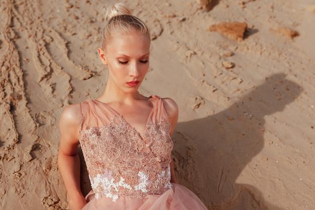 Close-up schoonheidsportret van een mooie blonde jonge vrouw poseren in borduurjurk in de woestijn, liggend op gouden zand met gesloten ogen. zonsondergang licht.