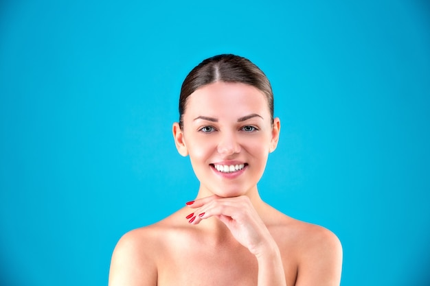 Close-up schoonheidsportret van jonge vrouwenbrunette die en haar gezicht op blauwe oppervlakte glimlachen aan te raken