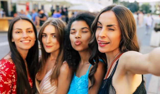 Close-up selfie foto van vier vriendinnen op vakantie, zomeroutfits dragen, kijken naar de camera, breed glimlachen en de tong uitsteken.