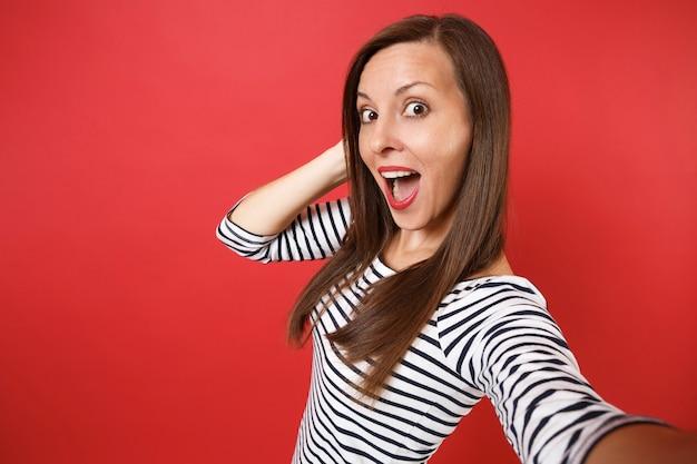 Close-up selfie-opname van een verbaasde jonge vrouw in gestreepte kleding die de mond wijd open houdt en er verbaasd uitziet