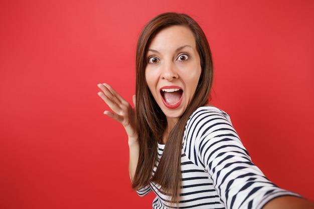 Close-up selfie-opname van opgewonden jonge vrouw die handen spreidt, mond wijd open houdt, verbaasd kijkt