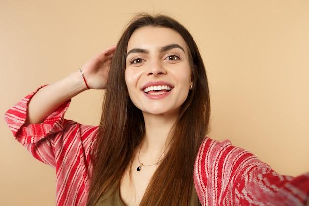 Close-up selfie shot van grappige jonge vrouw in casual kleding op zoek naar camera, hand op het hoofd zetten geïsoleerd op pastel beige achtergrond. mensen oprechte emoties, lifestyle concept. bespotten kopie ruimte.