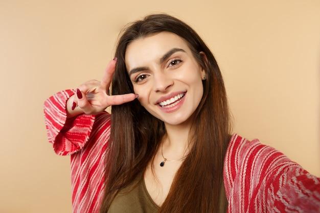 Close-up selfie shot van vrolijke jonge vrouw in casual kleding op zoek naar camera, overwinning teken geïsoleerd op pastel beige achtergrond tonen. mensen oprechte emoties, lifestyle concept. bespotten kopie ruimte.