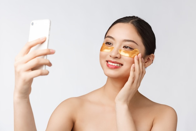 Close-up selfie van mooie gelukkige vrouw met oogmasker op gezicht vrouw met ogen masker nemen selfie met mobiele telefoon thuis genieten van ontspanning en