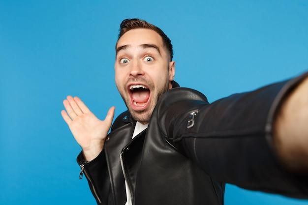 Close-up selfie van stijlvolle jonge ongeschoren man in zwart lederen jas wit t-shirt op zoek camera geïsoleerd op blauwe muur achtergrond studio portret. mensen oprecht emoties concept. bespotten kopie ruimte