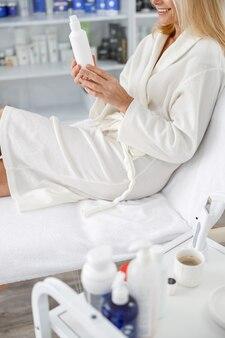 Close-up senior blanke vrouw glimlachend in witte badjas, met lotion pot in schoonheidssalon.
