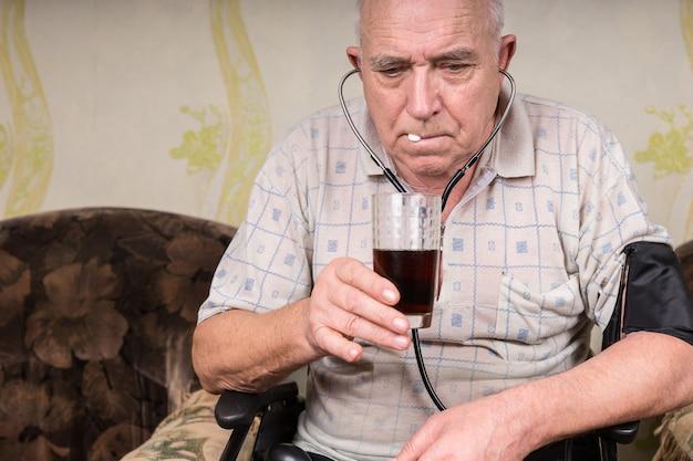 Close-up senior kale man met bp-apparaat bevestigd op zijn lichaam, zijn medicijn innemend met een glas sap in de woonkamer..