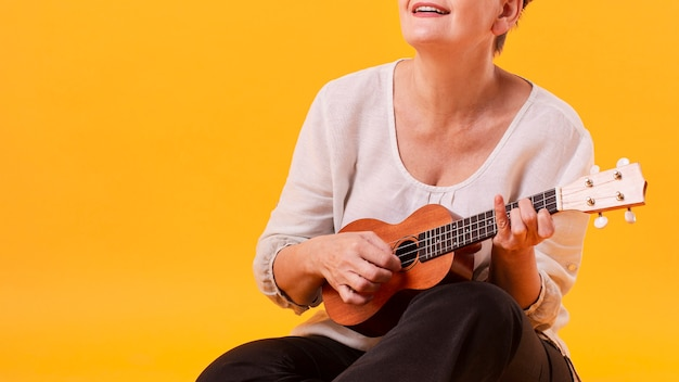 Close-up senior vrouw gitaar spelen