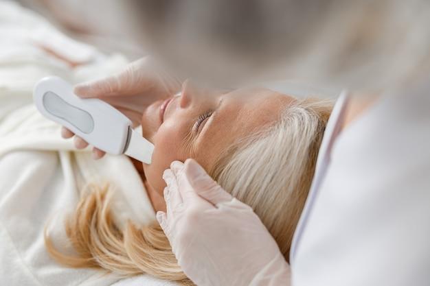 Close-up senior vrouw in professionele beauty spa salon tijdens ultrasone gezichtsreiniging procedure.