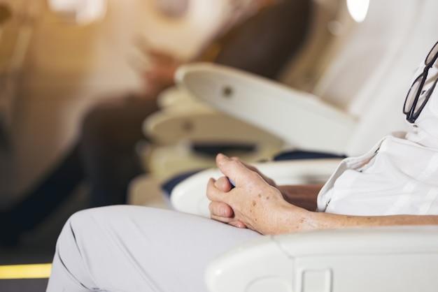 Close-up senior woman's hand zitten op vliegtuig