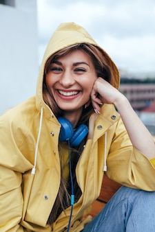 Close-up sensueel portret van het jonge het glimlachen het gelukkige vrouw stellen met blauwe oortelefoons openlucht