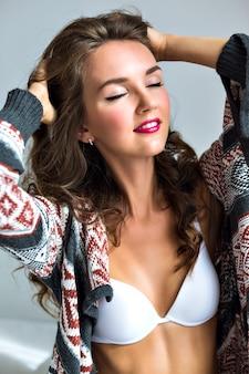 Close-up sensueel portret van mooie jonge vrouw met lichte krulharen, geniet van haar ochtend en ontspan, sluit haar ogen, draagt een eenvoudige witte beha en een gezellige trui.