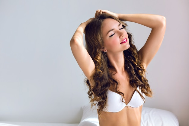Close-up sensuele sexy ochtendportret van prachtige jonge vrouw net wakker in witte slaapkamer, geniet van haar ochtendtijd, het dragen van leuke casual lingerie, een en stijlvolle make-up, zachte pastelkleuren.