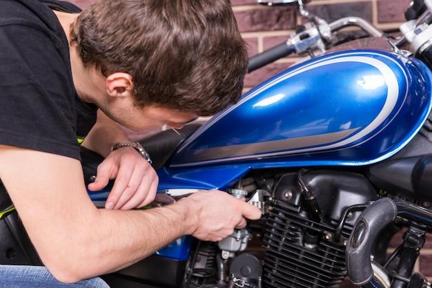 Close-up serieuze jonge kerel die zijn blauwe sportmotor repareert met behulp van een moersleutel.