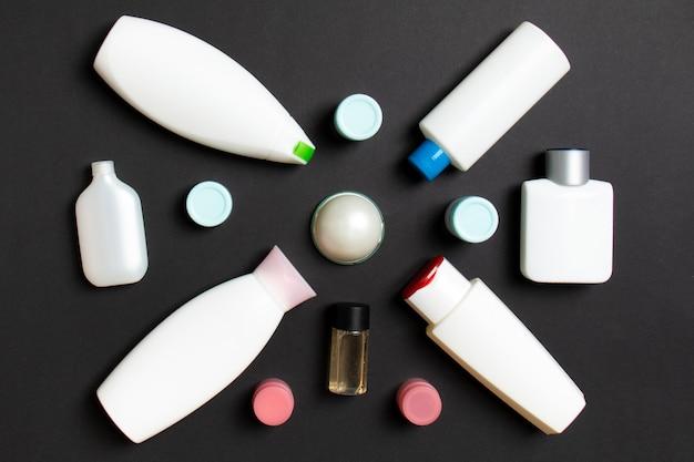 Close-up set van verschillende formaten flessen en potten voor cosmetische producten op gekleurde achtergrondkleur. gezichts- en lichaamsverzorgingsconcept met kopieerruimte.