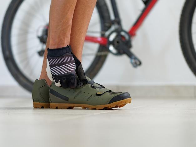 Close-up shot. fietser die mtb schoenen bindt dichtbij mountainbike.