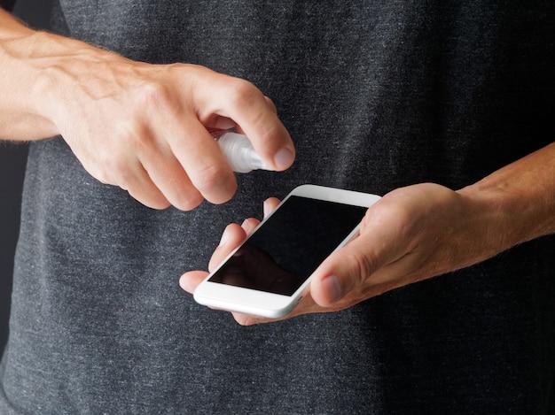 Close-up shot. man zijn smartphone touchscreen desinfecteren door een ontsmettingsmiddel uit een fles te spuiten.