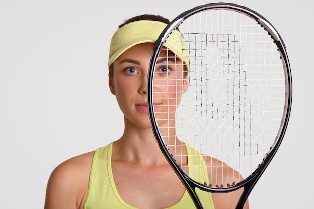 Close-up shot van aangenaam ogende gezonde vrouw houdt tennisracket, wordt runner up, kijkt door net, draagt court cap