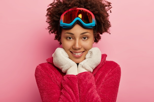Close-up shot van aangenaam ogende jonge vrouw met snowboard masker, houdt beide handen onder de kin, draagt warme witte handschoenen, kijkt direct naar de camera.