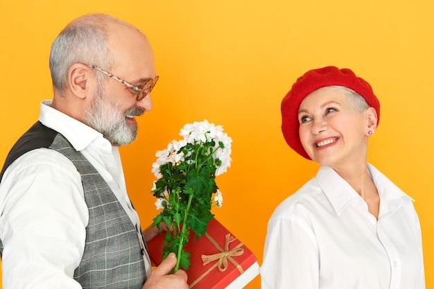 Close-up shot van aantrekkelijke bebaarde senior man in glazen geven zijn mooie elegante vrouw bos veld madeliefjes en doos met sieraden. rijpe vrouw voelt zich gelukkig met het ontvangen van bloemen van haar man