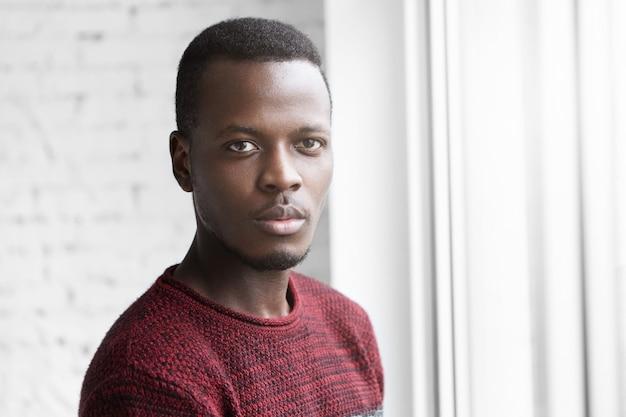 Close-up shot van aantrekkelijke jonge donkere man in casual trui staande bij raam