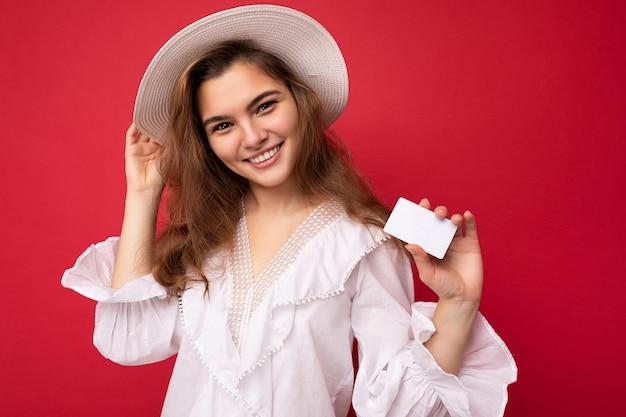 Close-up shot van aantrekkelijke positieve lachende volwassen donkere blonde vrouw, gekleed in witte blouse en witte hoed geïsoleerd over rode achtergrond met creditcard camera kijken.