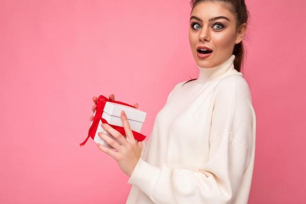 Close-up shot van aantrekkelijke positieve verbaasde jonge brunette vrouw geïsoleerd over roze muur muur