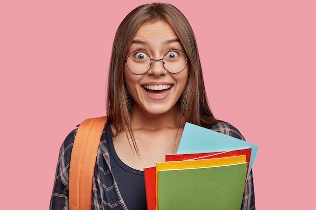 Close-up shot van aantrekkelijke student poseren tegen de roze muur met bril
