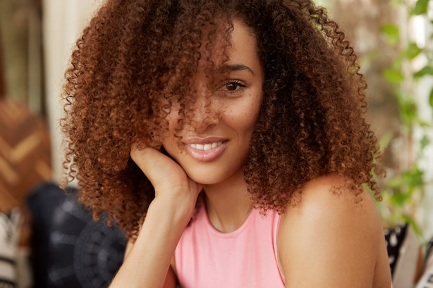 Close-up shot van aantrekkelijke vrouw met krullend haar en donkere huid, positieve uitdrukking heeft, besteedt vrije tijd in familiekring. vrouwelijke donkere huid student heeft rust na een vermoeide dag op de universiteit