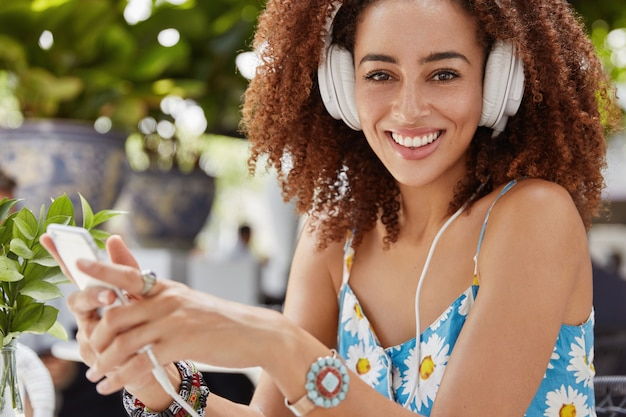Close-up shot van african american girl chats online met vrienden in sociale netwerken, surft op internetwebsite, luistert naar favoriete audionummer van afspeellijst in hoofdtelefoons