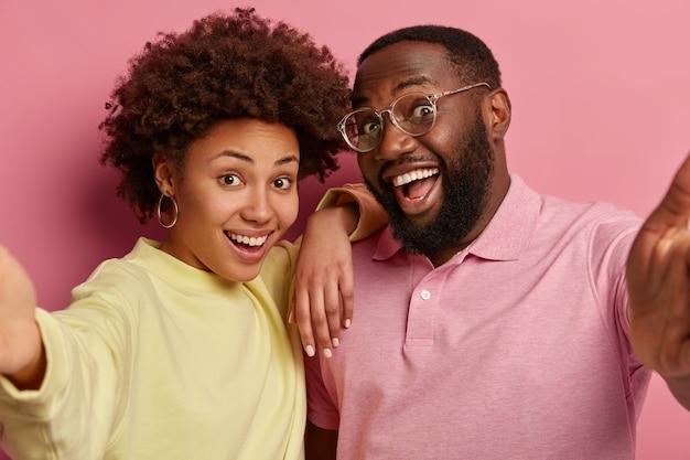 Close-up shot van afro-amerikaanse paar of vrienden verlengen handen en selfie maken