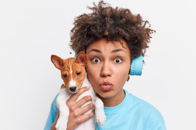 Close-up shot van afro-amerikaanse vrouwelijke hondeneigenaar draagt stamboom puppy houdt lippen gevouwen kijkt geschokt heeft krullend haar luistert muziek via koptelefoon tijdens het wandelen met favoriete dier
