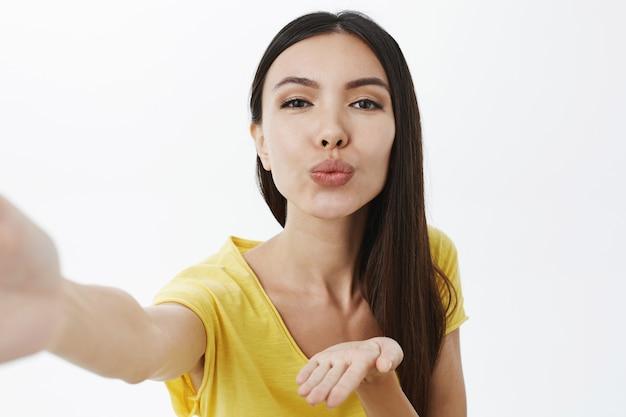 Close-up shot van assertieve knappe vrouw met donker haar hand naar camera trekken alsof ze een smartphone vasthoudt