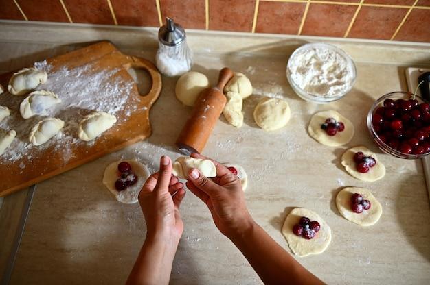Close-up shot van banketbakker hand beeldhouwen cherry dumplings op keuken aanrecht achtergrond. cherry knoedel liggend op het houten bord met verspreide bloem. proces van het stap voor stap koken van dumplings