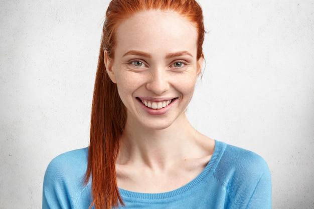 Close-up shot van blij gember vrouwtje heeft brede glimlach, witte tanden, sproeten huid, in goed humeur na een goede nachtrust tijdens vakantie