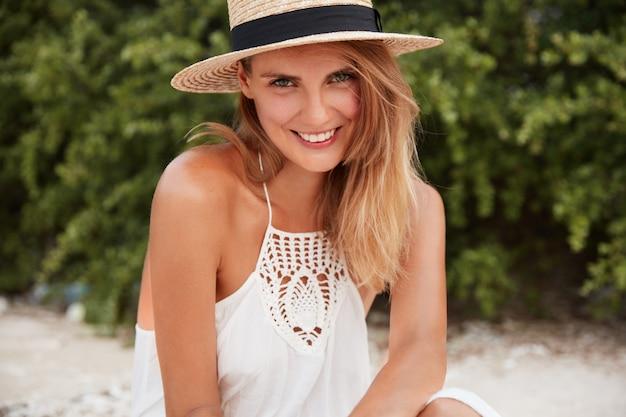 Close-up shot van blij lachend vrouwelijk model met blije uitdrukking draagt witte jurk en strooien hoed, vormt op het strand in de buurt van groene vegetatie, geniet van zomerzon en warm weer. gezichtsuitdrukkingen