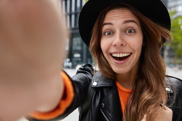 Close-up shot van blije vrouw draagt zwarte hoed, glimlacht breed, in hoge geest, heeft plezier tijdens wandeling buiten