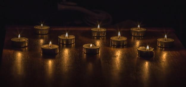 Close-up shot van brandende kaarsen op een houten tafel