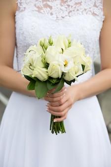 Close-up shot van bruid handen met mooie bruiloft boeket met groene rozen