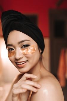 Close-up shot van bruinogige vrouw in handdoek op haar hoofd en met patches