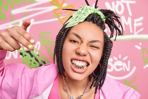 Close-up shot van brutale afro-amerikaanse vrouw balde gouden tanden maakt yo gebaar voelt cool heeft gekamd dreadlocks gekleed in jas poses tegen kleurrijke graffiti muur