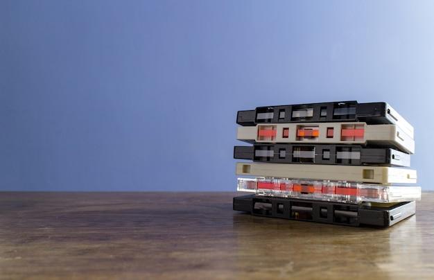 Close-up shot van cassettebandjes op een houten tafel met een blauwe muur