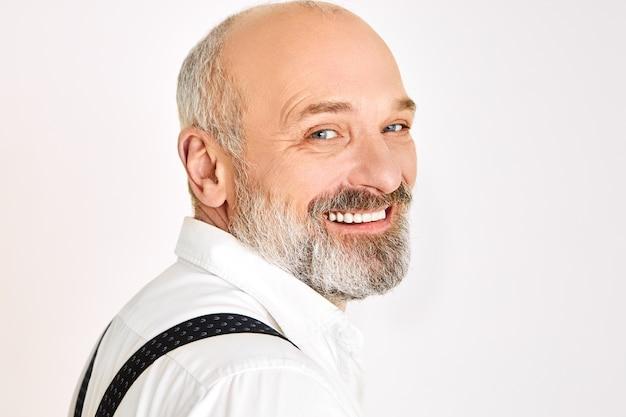 Close-up shot van charismatische vrolijke europese mannelijke gepensioneerde m / v met borstelige baard elegante stijlvolle kleding dragen bij speciale gelegenheid in goed humeur, camera kijken met brede stralende glimlach