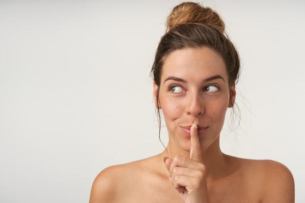 Close-up shot van charmante jonge vrouw stil gebaar maken, opzij kijken met positieve emoties, broodje kapsel en geen make-up dragen