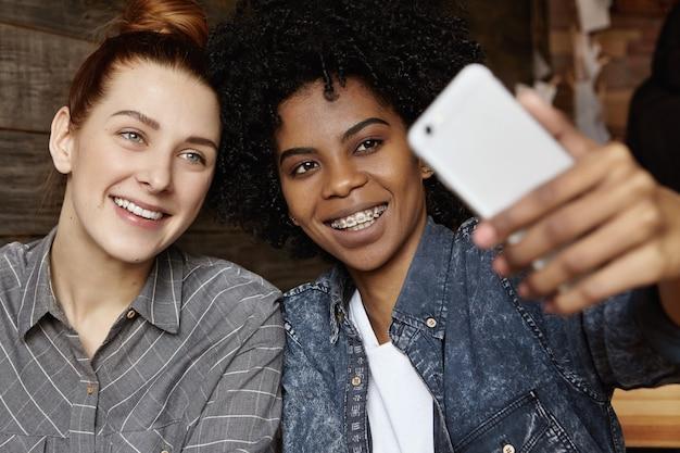 Close-up shot van charmante roodharige lesbienne met haarknoop samen poseren voor selfie