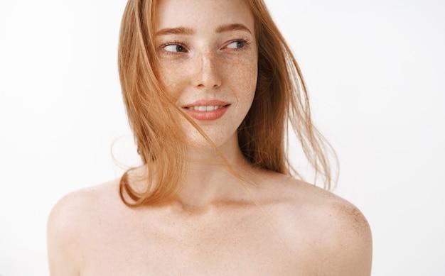 Close-up shot van charmante sensuele en vrouwelijke roodharige vrouw met sproeten poseren naakt, teder en zacht draaiend naar rechts, flirterig en opgetogen staan