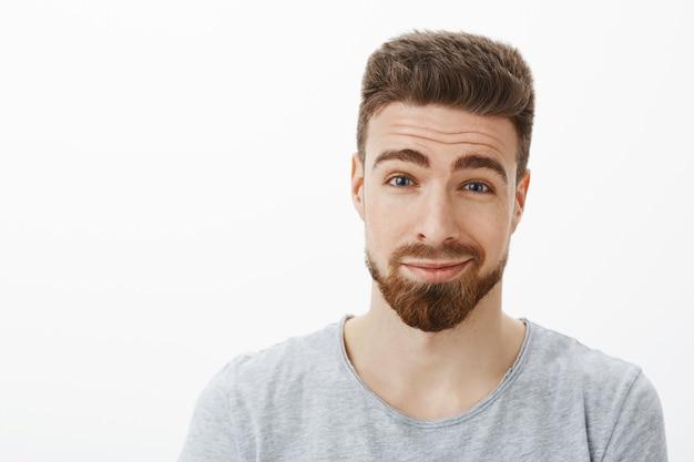 Close-up shot van charmante vriendelijke en charismatische gelukkig bebaarde man met snor wenkbrauwen optrekken en grijnzend van verrukking en tedere gevoelens die met liefde en vreugde opkijken