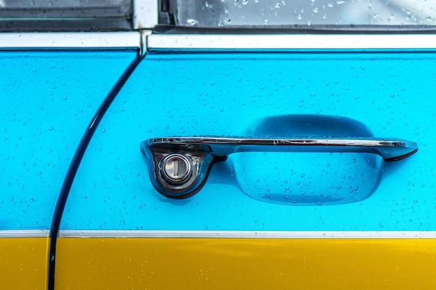 Close-up shot van de deurklink van een blauwe en gele auto