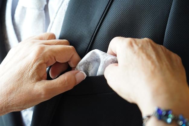 Close-up shot van de gerimpelde handen van een vrouw die de zakdoek van een bruidegom bevestigt