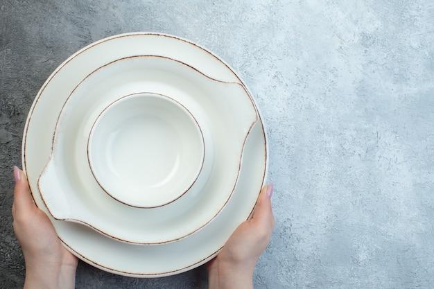 Close-up shot van de hand met wit servies aan de rechterkant op een half donker lichtgrijs oppervlak met een verontrust oppervlak